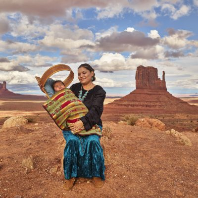 Navajo Eula Matene hold three-month-old Leon Clark on a ridge in the Arizona portion of Monument Valley, a red-sand desert region on the Arizona-Utah border known for the towering sandstone buttes of Monument Valley Navajo Tribal Park. The park, frequently a filming location for Western movies, is accessed by the looping, 17-mile Valley Drive. The famous, steeply sloped Mittens buttes can be viewed from several overlooks.